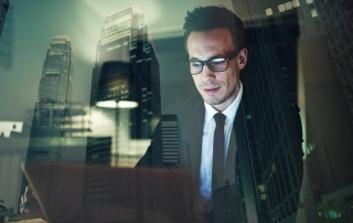 Optimistic businessman working on laptop at office in the night, Working overtime with big city in background