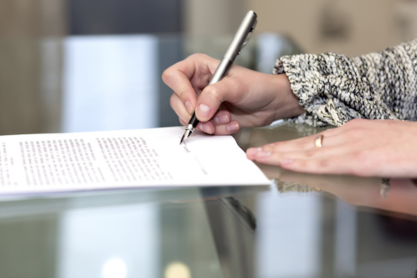 Close up of female hand signing formal paper