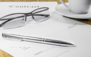 contract business papers pen glasses cup of coffee