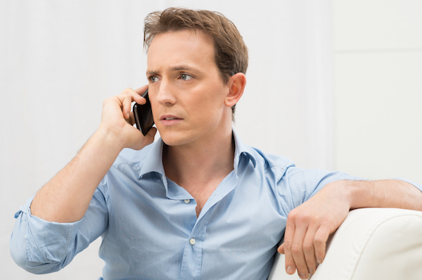 Man on phone looking worried, IRS tax scam