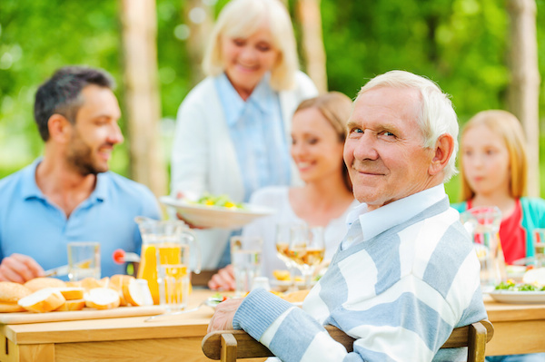 Family having dinner outside, older man looking at camera, blended family, estate planning attorney