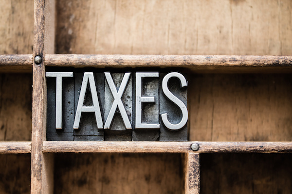 Taxes letterpress letters on wooden shelf, IRS rule changes