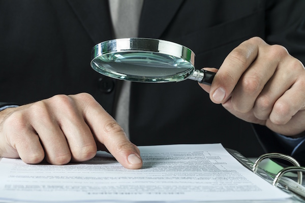Man with magnifying glass auditing documents, audit advice from tax attorney