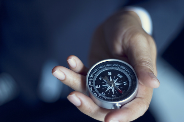 Businessman with a compass holding in hand, color tone film look